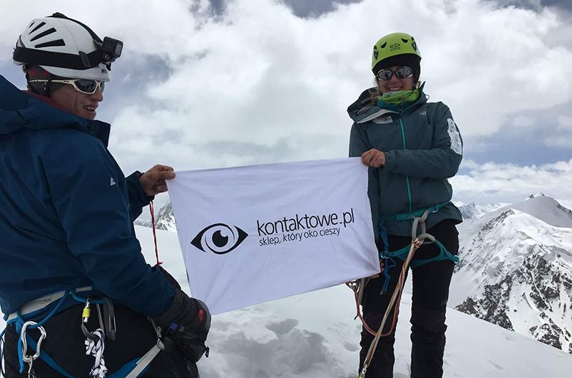 Dwóch uczestników wyprawy do Karakorum trzyma flagę kontaktowe.pl na tle gór.