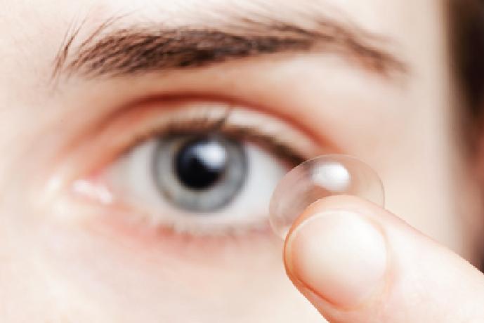 Zdjęcie przedstawia proces zakładania soczewki kontaktowej na oko.