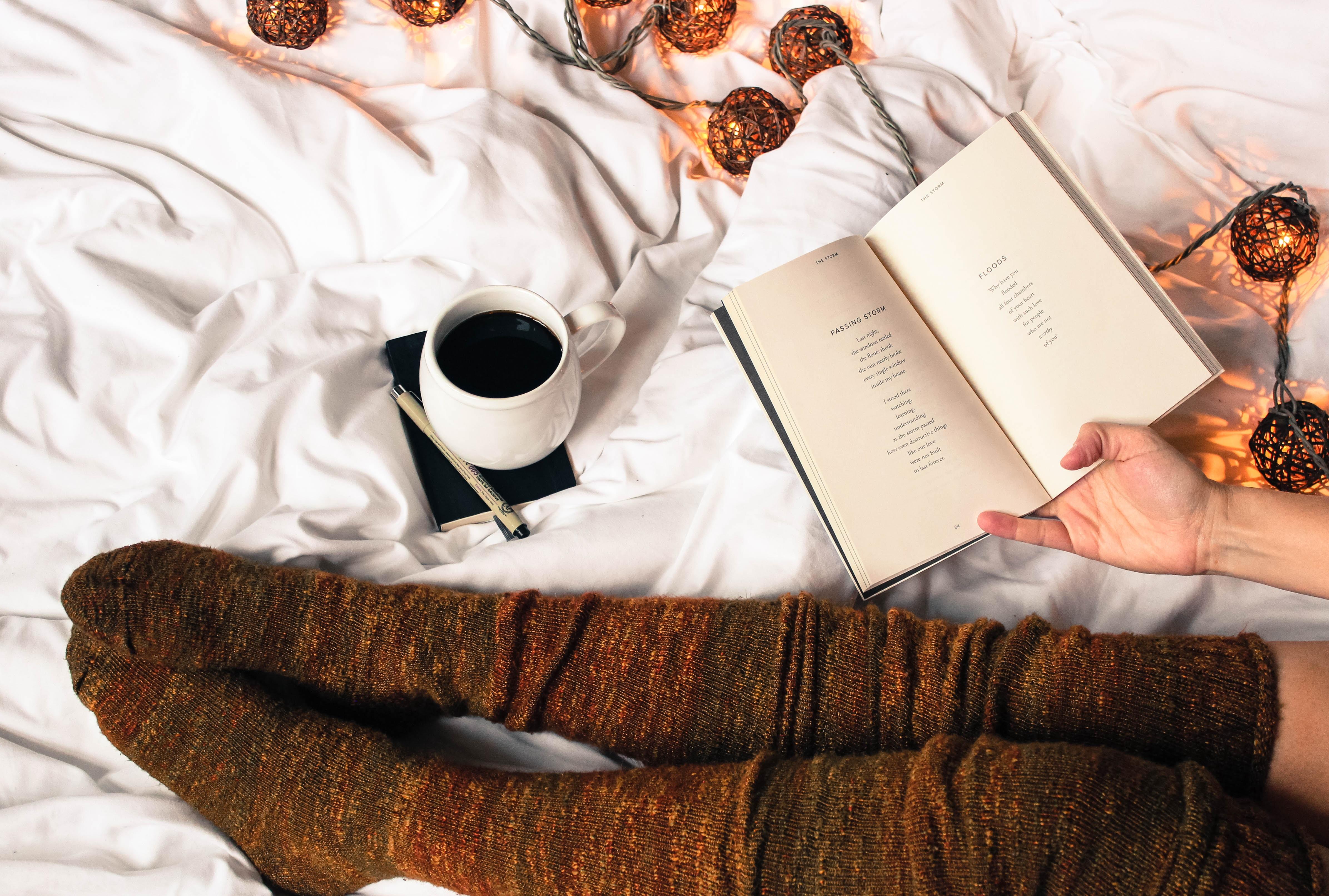 Łóżko na którym siedzi kobieta pijąca kawę i czytająca książke